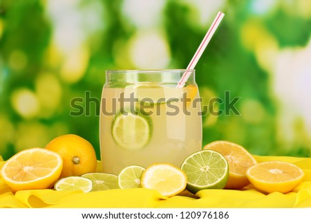 Citrus lemonade in glass bank of citrus around on yellow fabric on natural background