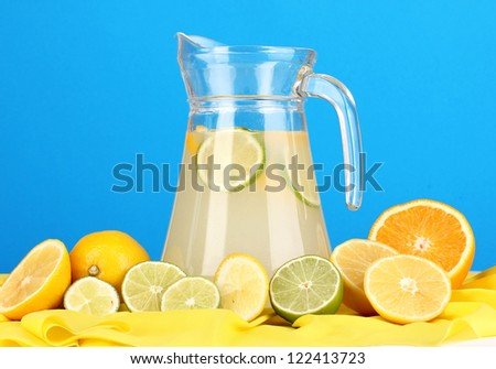 Citrus lemonade in glass pitcher of citrus around on yellow fabric on blue background