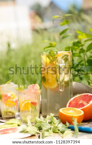 citrus lemonade in glass with mint. Orange. Grapefruit and lemon. On greenery background. #1128397394