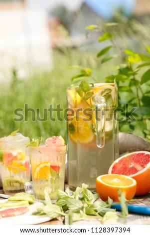 citrus lemonade in glass with mint. Orange. Grapefruit and lemon. On greenery background. #1128397394
