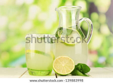 Citrus lemonade in pitcher and glass on wooden table on natural background