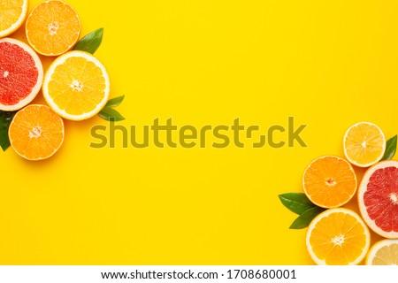 Citruses fruits on Illuminating pantone colored  background with copyspace, fruit flatlay, summer minimal compositon with grapefruit, lemon, mandarin and orange, color of year 2021