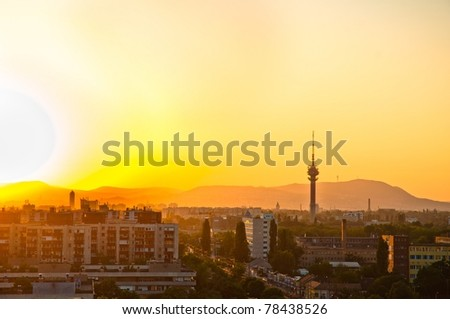 City at dawn with apartments and tower and mountains - stock photo