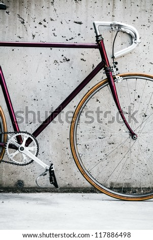 City bicycle fixed gear and concrete wall, vintage style closeup on bike frame, vintage old retro bike, cycling or commuting in city urban environment, ecological transportation concept