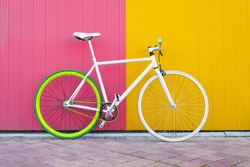 City bicycle fixed gear on yellow and red wall. Cycling or commuting in city urban environment, ecological transportation concept.