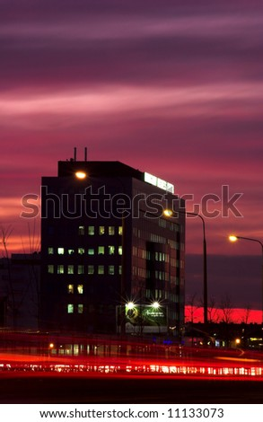 City building in sunset with blurred traffic lights