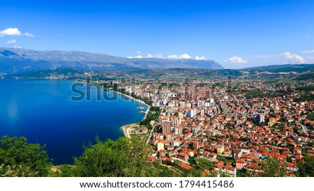 City buildings with red roofs at the shore of a lake with mountains in the background. View of Pogradec city and Ohrid lake, Pogradec, Albania. Stock photo ©