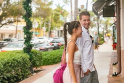 City couple happy in love young man and woman walking on street shopping looking at shop stores talking together, Naples, Florida, USA travel vacation.