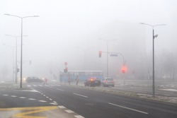 City crossroads with stoplights and pedestrians in the fog. Bad weather condition in winter, poor visibility.  Increased pollution.