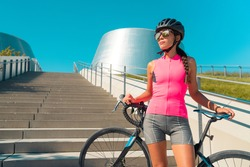 City cyclist woman with road bike. Girl wearing helmet, sunglasses, pink jersey for biking on hot summer day urban commute ride. Cycling concept.