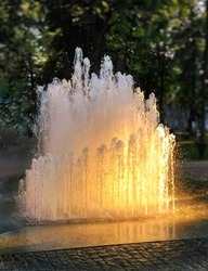 City fountain in the rays of the setting sun
