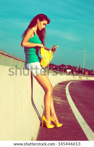 city girl in green top tank shorts and high heel shoes on the street day shot
