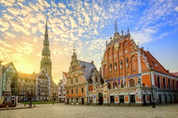 City Hall Square with House of the Blackheads and Saint Peter church in Old Town of Riga on dramatic sunrise, Latvia