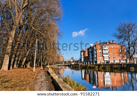 City house above the river canal near the old park. Late autumn urban landscape