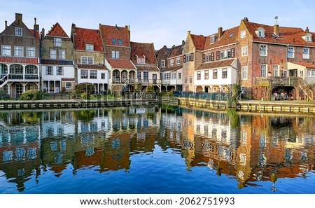 City houses are reflected in the river water. Town houses reflected in water. Houses reflected in water
