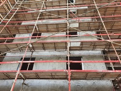 City housing renovation project. Construction site. Red scaffoldings. Wooden platforms. Gray wall. Closeup. National outline plan. NOP - TAMA 38. Tel Aviv, Israel.