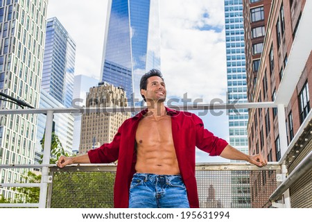 City Hunk.  Wearing a long sleeve red shirt, unbuttoned,  a handsome, strong, sexy, middle age guy is standing in the middle of high buildings, confidently looking forward.