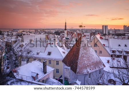 City landscape with snow-covered tiled roofs of old city and town hall steeple at sunset on frosty winter day. Tallinn, Estonia Stock fotó ©