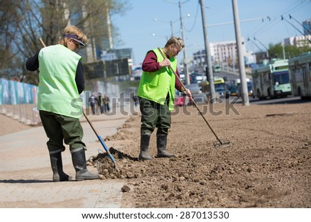 City landscapers female workers preparing soil along street for grass planting with rake tools
