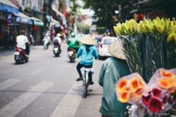 City life in street of old quarter in Hanoi. Flower vendor in traditional  conical hat, Vietnam.