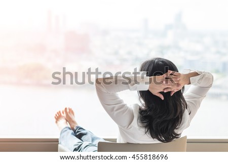 City lifestyle happy easy simple living day time life style: Rear back view of Asian business working woman w/ hands behind head looking toward awesome urban background sitting in home office building
