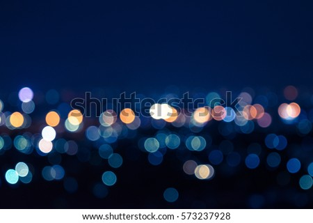 City light at night abstract blur cityscape with bokeh landscape urban skyline, blurry building and street nightlife with blue color sunset, glow circle lens flare on road, dark black twilight town.