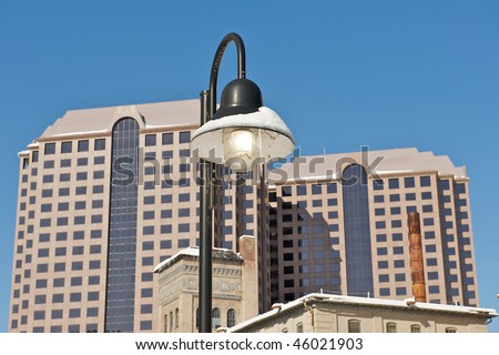 City light post with icicles hanging from it.  Architectural buildings in the background surrounded by a blue sky.