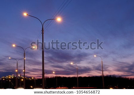 Stock Photo city lighting poles off the road, evening landscape