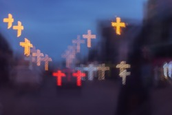 City lights are blurry, with a cross-shaped bokeh background.car on the road at night,cross symbol.