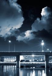 City night scene of bridge with dramtic clouds in sky.