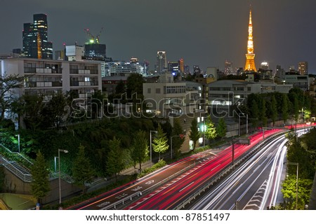 City nights scene with car motion lights and Tokyo Tower on the background, Japan