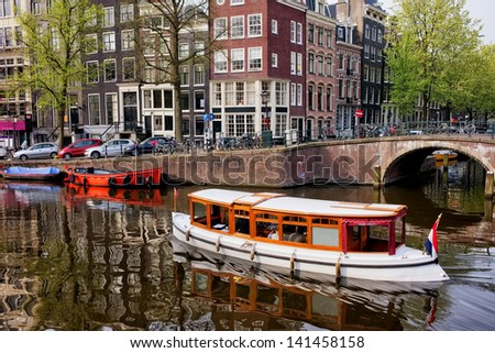City of Amsterdam in Holland picturesque scenery, boats on a canal and historic terraced houses.
