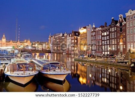 City of Amsterdam in Netherlands at night, historic apartment houses with reflections on water and boats ready for canal tours and cruises.