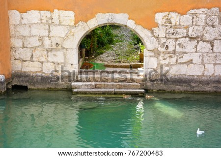 City of Annecy. The passage opens to the water of the Tue Canal in the wall of a medieval historic house in the historic and tourist resort town of Annecy in France. #767200483