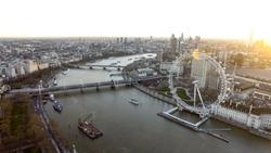 City of London Skyline High Angle Aerial View of London Eye Wheel, Thames River, Hungerford Bridge, Whitehall Gardens along the Riverside at Sunset