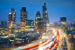 City of London view at sunset and busy road with transport blurred lights. Success, transformation and innovation idea.
