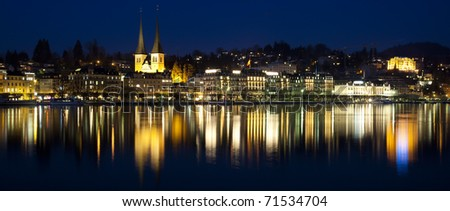 City of Luzern, Switzerland, showing the famous Chapel Bridge reflected in the water at twilight, sundown
