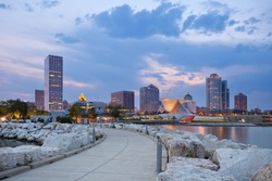 City of Milwaukee skyline. Image of Milwaukee skyline at twilight with city reflection in lake Michigan and harbor pier.