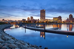 City of Milwaukee skyline. Image of the Milwaukee skyline at twilight with city reflection in lake Michigan and harbor pier.