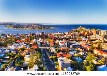 City of Newcastle in Australia north from Sydney - Hunter river mouth to Pacific ocean. CBD of industrial hub and sea port with local streets and houses around the Cathedral of Newcastle.