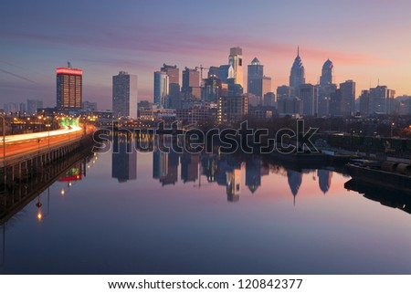 City of Philadelphia. Image of Philadelphia skyline in a morning mist, Schuylkill River and busy highway leading in to the city during sunrise.
