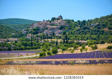 City of Saint-Saturnin-les-Apt on the hill with lavender fields in valley on summer day. Provence, France Stockfoto ©