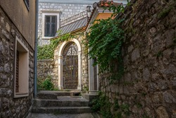 City of stairs. Mysterious gate. A cute old town attraction. Lovely alley. Old town streets. City maze. Really a lovely town. Narrow Streets of Old Town in Herceg Novi. Walls overgrown with ivy.