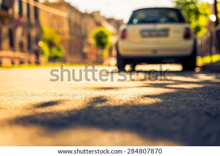 City on a sunny day, a quiet street with trees and parking car. View from the level of asphalt, image in the yellow-blue toning #284807870