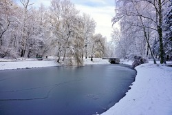City park in winter scenery. Beautiful little pond in winter.