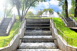 city park landscape with waterfall step dam against blue sky with clouds background. People enjoying sunny day in city park with fountain pond. Summer in Moscow city Russia