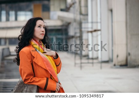 City portrait of gorgeous girl with black curly hair in orange cloak and varicolored bright scarf. Girl look in distance in profile on background of building. Dreaming gaze of beautiful female eyes. #1095349817