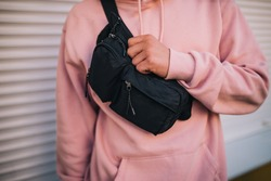 City portrait of handsome hipster guy wearing pink blank hoodie with black waist bag with space for your logo or design. Mockup for print