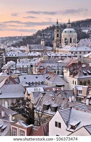 City roofs covered with snow below a pink sky, Prague, Czech Republic