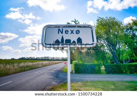 City sign of Nexø city on the danish island of Bornholm in the summer under a blue sky #1500734228